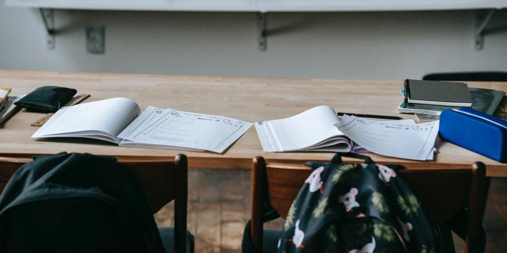 Eine Schulbank mit Unterlagen vor der zwei Stühle mit Rucksäcken stehen - Visions4Children